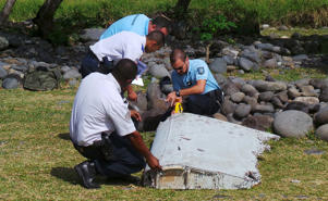 File picture shows French gendarmes and police inspecting a large piece of plane debris which was found on the beach in Saint-Andre, on the French Indian Ocean island of La Reunion.