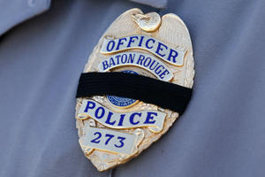 A Baton Rouge police officer's badge is seen with a black band during a funeral service for police officer Matthew Gerald at Healing Place Church in Baton Rouge, Louisiana, July 22, 2016.