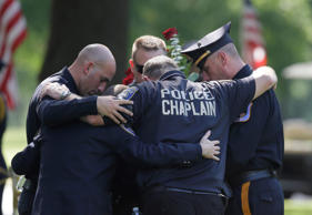 Law enforcement officers embrace each other as they pray after the graveside service for Dallas Police Sgt. Michael J. Smith at Restland Funeral Home and Cemetery in Dallas, Thursday, July 14, 2016.