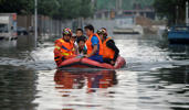 In this Thursday, July 21, 2016, photo, rescuers use a raft to transport people along a flooded street in Shenyang in northeastern China's Liaoning Province.