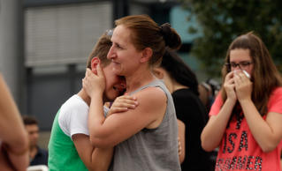 People mourn near the crime scene outside the OEZ shopping center the day after a shooting spree left nine victims dead on July 23, 2016 in Munich, Germany.