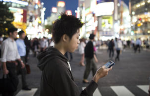 Ayato, 19, plays the Pokemon Go game on his smartphone on July 22, 2016 in Tokyo, Japan.