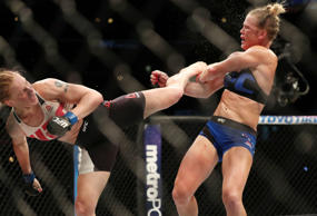 Holly Holm (red gloves) cis kicked by Valentina Shevchenko (blue gloves) in their women's bantamweight bout during UFC Fight Night at United Center.