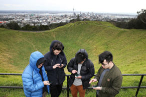 Zijia Ge (L) Jack Zheng (CL) Ky Pham (CR) and Tony Sun (R) search for Pokemon on the top of Mount Eden.
