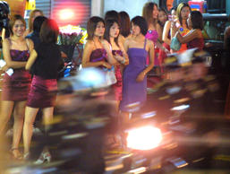 Young Thai prostitutes stand on a the side of a street waiting for customers as ...