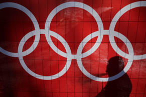 In this Feb. 15, 2014 file photo the shadow of a man is cast on the Olympic rings as he smokes at the Rosa Khutor Alpine Center, at the 2014 Winter Olympics in Krasnaya Polyana, Russia.