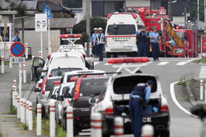 Police officers stand by with ambulances and firetrucks seen on a street near a facility for the handicapped where a number of people were killed and dozens injured in a knife attack Tuesday, July 26, 2016, in Sagamihara, outside Tokyo.