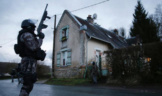 File: Members of the French GIPN intervention police forces secure a neighbourhood in Corcy, northeast of Paris January 8, 2015.