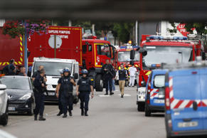 French police officers and firemen arrive at the scene of a hostage-taking at a church in Saint-Etienne-du-Rouvray, northern France, on July 26, 2016 that left the priest dead. A priest was killed on July 26 when men armed with knives seized hostages at