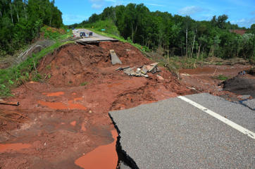 People observe part of Wisconsin Highway 13, washed out after heavy rains, south of Highbridge in Ashland, Wis., Tuesday, July 12, 2016. Storms carrying tornadoes, torrential rain and powerful winds damaged homes, deposited a snowplow in a tree and flood