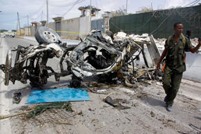 File: Somali soldier stand near the wreckage of a car bomb outside the UN's office in Mogadishu, Somalia, Tuesday, July 26, 2016.