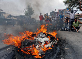 File: Masked demonstrators shout slogans next to a burning tyre during a protest in Srinagar against the recent killings in Kashmir, July 26, 2016.