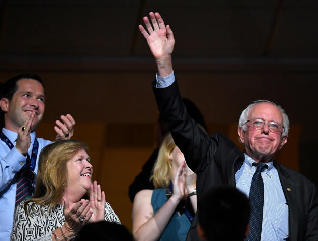 Sen. Bernie Sanders, I-Vt., right, waves as he acknowledges applause during the second day of the Democratic National Convention in Philadelphia , Tuesday, July 26, 2016.