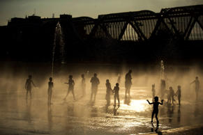 People cool themselves off in a public water fountain next to the Manzanares river during a warm summer day in Madrid, Tuesday, July 26, 2016. Temperatures reached 38 degrees Celsius (100 Fahrenheit) in the Spanish capital. (AP Photo/Francisco Seco)