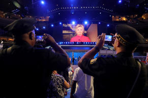 A screen displays Democratic presidential candidate Hillary Clinton delivering r...