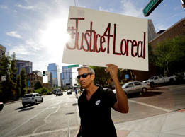 FILE - In this Monday, July 25, 2016 file photo, Chris Fleischman protests outside Maricopa County Attorney Bill Montgomery's office in Phoenix. Loreal Tsingine, a Navajo woman who was fatally shot by an Arizona police officer earlier this year, had medical scissors in her hand as she approached the lawman, body camera video released Wednesday shows. The shooting led tribal officials to urge the U.S. Justice Department to investigate the treatment of American Indians who live in towns bordering the reservation.
