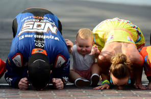 Kyle Busch, driver of the NOS Energy Drink Toyota, kisses the bricks with his wife, Samantha, and son, Brexton, after winning the NASCAR XFINITY Series Lilly Diabetes 250 at Indianapolis Motor Speedway on July 23.