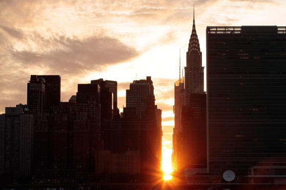 A view of the 'Manhattanhenge' sunset from Hunters Point South Park, July 11, 2016 in the Queens borough of New York City.