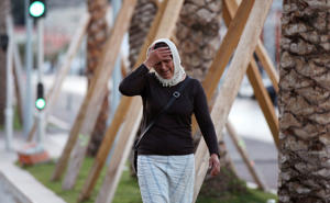 A woman cries asking for her son as she walk near the scene of an attack after a truck drove onto the sidewalk and plowed through a crowd of revelers who'd gathered to watch the fireworks in the French resort city of Nice, southern France, Friday, July 1