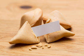 A group of fortune cookies with message note on wooden table. Taken in Studio with a 5D mark III.