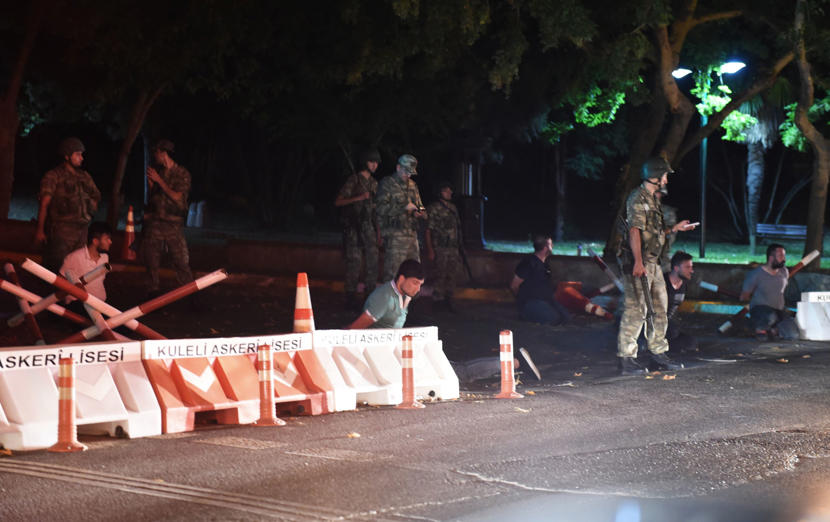 Turkish security officers detain police officers on the side of the road on July 15, 2016 in Istanbul, during a security shutdown of the Bosphorus Bridge.  Turkish Prime Minister Binali Yildirim on July 15 denounced what he said was an 'illegal attempt'