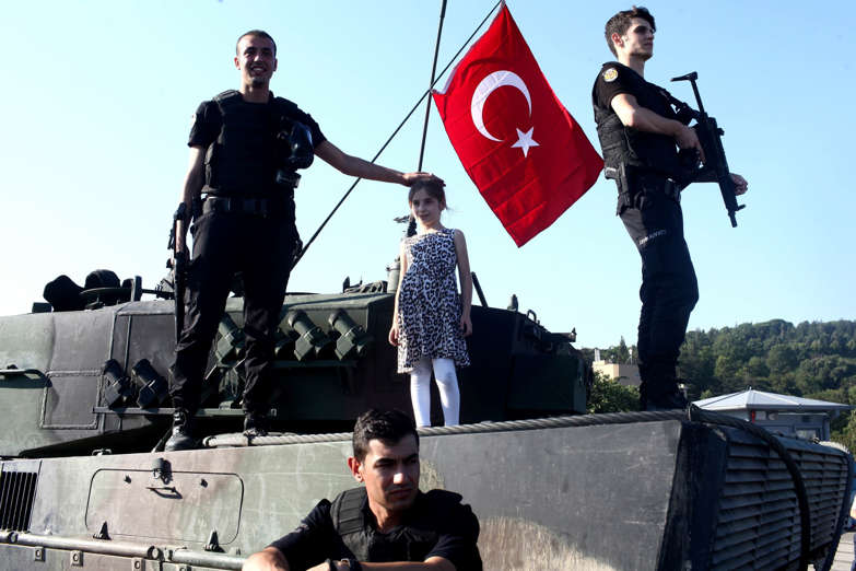 ISTANBUL, TURKEY - JULY 16: People gather for celebration around Turkish police officers, loyal to the government, standing atop tanks abandoned by Turkish army officers, against a backdrop of Istanbul's iconic Bosporus Bridge in Istanbul, July 16, 2016,