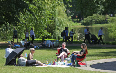 People enjoy the hot weather in St James's Park in London, as a mini heatwave brings the hottest temperatures of the year.