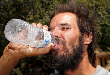 Michael Martinez drinks a bottle of water at a Salvation Army hydration station in an effort to beat rising temperatures, expected to reach 115-degrees Monday, June 20, 2016, in Phoenix.
