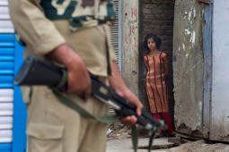 File: In this Sunday, July 17, 2016 photo, a Kashmiri girl watches an Indian paramilitary soldier standing guard during curfew in Srinagar, Indian controlled Kashmir.