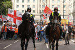 LONDON, UK - JULY 16 : Horse monuted police lead the EDL mark on Park Lane. About a hundred members of The English Defence League (EDL) march on Park Lane for a rally in Hyde Park. The march on 16 July 2016 was heavily policed keeping the group away from the public. (Photo by David Mbiyu/Corbis via Getty Images)