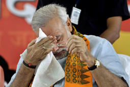 File: Gujarat state Chief Minister Narendra Modi who is on the third day of his fast wipes his face in Ahmadabad, India, Monday, Sept. 19, 2011.