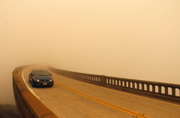 Smoke from the Soberanes Fire combined with a marine layer reduces visibility over Bixby Bridge on State Route 1 north of Big Sur, California, July 26, 2016.