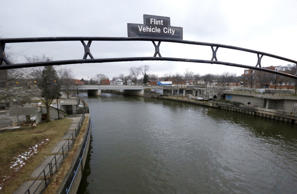 FILE - This Jan. 26, 2016, file photo shows a sign over the Flint River in Flint, Mich.