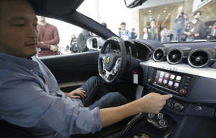An Apple employee gives a demonstration of CarPlay in a Ferrari at the Apple Worldwide Developers Conference in San Francisco, Monday, June 2, 2014.