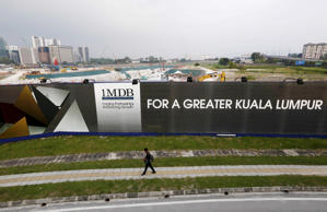 A man walks past a 1 Malaysia Development Berhad (1MDB) billboard at the funds flagship Tun Razak Exchange development in Kuala Lumpur, March 1, 2015.
