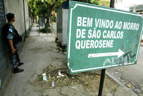 "A Brazilian policeman takes up a position near a signs that reads: ""Welcome to Sao Carlos Querosene Slum"" at the Rio Comprido neighborhood in Rio de Janeiro, October 13, 2004."