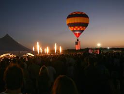 "Flames are seen from the burners of several hot air gondolas, without their balloon envelopes attached, and the American Flag is flown under another balloon as part of the opening ceremonies and ""balloon glow"" event of the 32nd ""Great Texas Balloon Race"" in Longview, Texas on Friday night, July 30, 2010. (AP Photo/Dr. Scott M. Lieberman)"