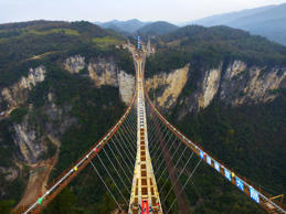 ZHANGJIAJIE, CHINA - DECEMBER 03:  (CHINA OUT) Aerial view of the glass-bottom bridge with steel beams completed at Tianmenshan National Forest Park on December 3, 2015 in Zhangjiajie, Hunan Province of China. World's longest glass-bottom bridge between