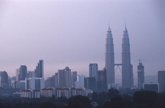 Diapositive 1 sur 44: KUALA LUMPUR, MALAYSIA - 1997/03/01: A view of the city skyline with the Petronas Towers in the early morning mist.. (Photo by Peter Charlesworth/LightRocket via Getty Images)