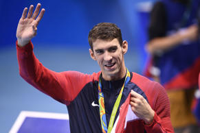 USA's gold medallist Michael Phelps waves after the podium ceremony of the Men's swimming 4 x 100m Medley Relay Final at the Rio 2016 Olympic Games at the Olympic Aquatics Stadium in Rio de Janeiro on August 13, 2016.   / AFP / Martin BUREAU        (Phot