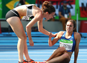 Abbey D'Agostino of the United States (R) is assisted by Nikki Hamblin of New Zealand