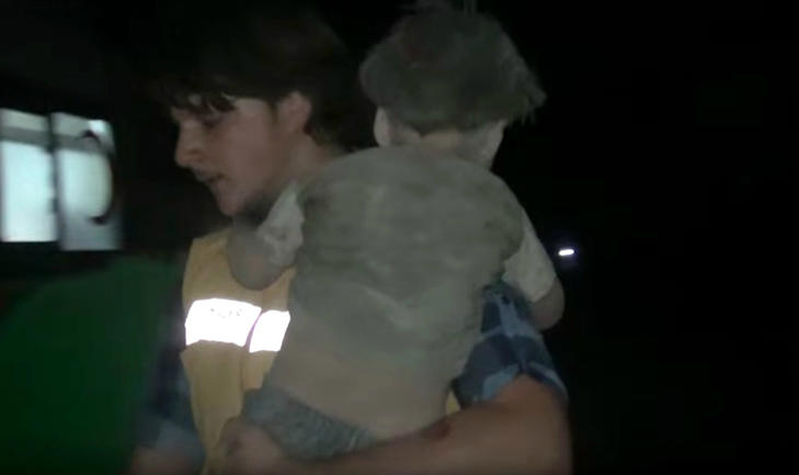 Five-year-old Syrian boy Omran Daqneesh being carried away by a paramedic after suffering injuries from a blast
