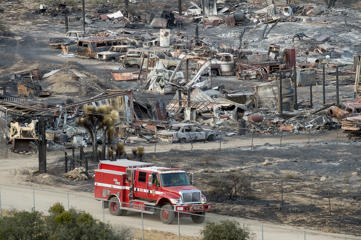 A firetruck passes scorched cars and trailers burned by the Blue Cut fire in Phelan, Calif., on Friday, Aug. 19, 2016. More people returned to their homes Friday as firefighters made significant progress against a huge wildfire burning in Southern California's San Bernardino National Forest, but that was tempered by the announcement that at least 96 homes and 213 outbuildings were destroyed.
