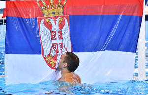 A player from Serbia kisses the Serbian flag after defeating Croatia in the men's water polo gold medal match during the Rio 2016 Summer Olympic Games at Olympic Aquatics Stadium.