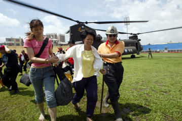 Residents are escorted from a helicopter in Tungshih town in central Taichung County, which is a base for rescue workers helping refugees from severe flooding in the wake of Typhoon Mindulle on July 6, 2004.