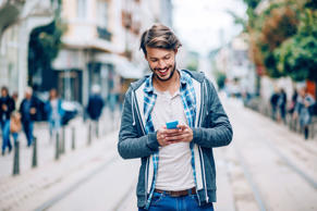 Happy man with smart phone text messaging.