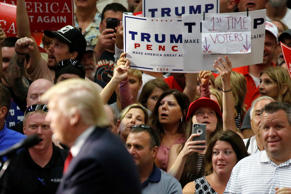 People hold up a sign claiming to be first time voters as Republican presidential nominee Donald Trump speaks onstage during a campaign rally in Akron, Ohio, U.S., August 22, 2016.