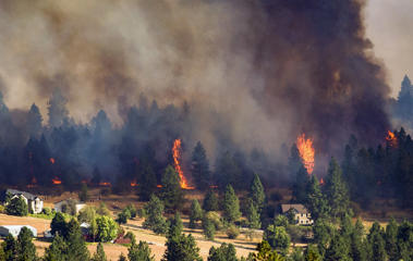 In this Sunday, Aug. 21, 2016 photo, a fast-moving wildfire approaches homes on the north side of Beacon Hill in Spokane, Wash. A series of fires started Sunday afternoon amid high winds and temperatures in the 90s.