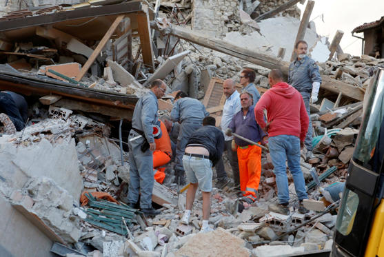 Rescuers works after a quake hit Amatrice.