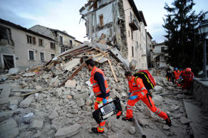 Rescuers search a crumbled building in Arcuata del Tronto, central Italy, where a 6.1 earthquake struck just after 3:30 a.m., Wednesday, Aug. 24, 2016. The quake was felt across a broad section of central Italy, including the capital Rome where people in homes in the historic center felt a long swaying followed by aftershocks.